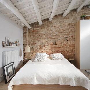 Modelo de dormitorio mediterráneo con paredes blancas y suelo de madera clara