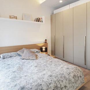 Modelo de habitación de invitados mediterránea con paredes blancas, suelo de madera en tonos medios y suelo beige