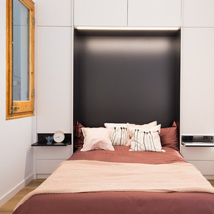 Small contemporary mezzanine bedroom in Barcelona with white walls, light hardwood flooring, no fireplace and brown floors.