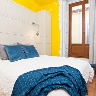 Foto de dormitorio principal, mediterráneo, sin chimenea, con paredes amarillas y suelo de madera en tonos medios