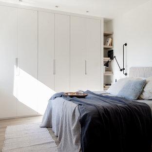 Foto de dormitorio contemporáneo con paredes blancas, suelo de madera en tonos medios y suelo marrón