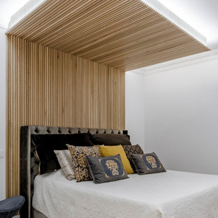 Foto de dormitorio madera, contemporáneo, madera, con paredes blancas, suelo de madera en tonos medios, marco de chimenea de madera, suelo marrón y madera