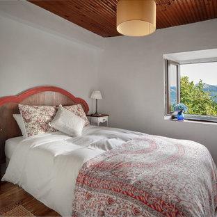 Imagen de habitación de invitados rural, de tamaño medio, con paredes blancas, suelo de madera oscura y suelo marrón