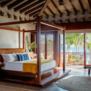 Foto de dormitorio abovedado y madera, tropical, con paredes beige, suelo de madera en tonos medios y suelo marrón