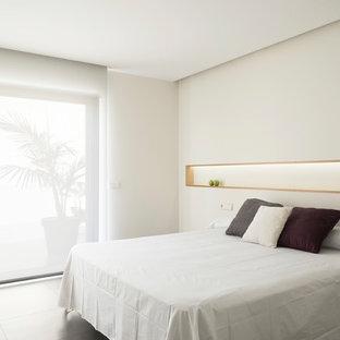 Modelo de dormitorio moderno con paredes blancas y suelo gris