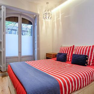 Ejemplo de dormitorio actual, de tamaño medio, sin chimenea, con paredes blancas y suelo de madera en tonos medios