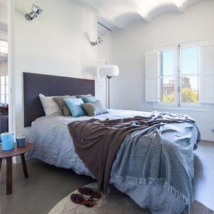 Imagen de dormitorio principal, actual, de tamaño medio, sin chimenea, con paredes blancas, suelo de cemento y suelo gris