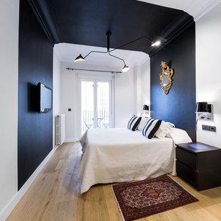 Modelo de dormitorio principal, actual, grande, sin chimenea, con paredes negras y suelo de madera clara