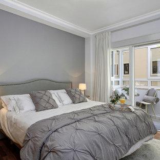 Modelo de dormitorio principal, tradicional renovado, de tamaño medio, con paredes azules, suelo de madera en tonos medios y suelo marrón