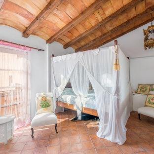 Ejemplo de dormitorio principal, mediterráneo, de tamaño medio, sin chimenea, con paredes blancas y suelo de baldosas de terracota