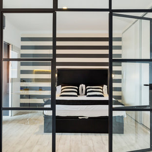 This is an example of a medium sized contemporary master bedroom in Palma de Mallorca with multi-coloured walls, light hardwood flooring and no fireplace.