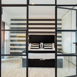 Cette image montre une chambre parentale design de taille moyenne avec un mur multicolore, un sol en bois clair et aucune cheminée.