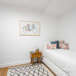 Ejemplo de habitación de invitados escandinava, sin chimenea, con paredes blancas y suelo de madera en tonos medios