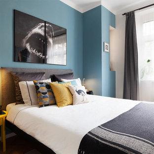 Modelo de dormitorio principal, nórdico, pequeño, con paredes azules, suelo de madera en tonos medios y suelo marrón