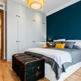 Foto de dormitorio nórdico con paredes azules, suelo de madera clara y suelo beige