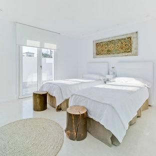 Ejemplo de habitación de invitados contemporánea, de tamaño medio, sin chimenea, con paredes blancas y suelo beige