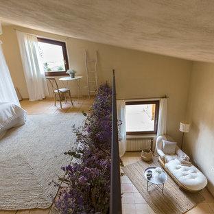 Ejemplo de dormitorio tipo loft, campestre, grande, sin chimenea, con paredes beige y suelo de baldosas de terracota