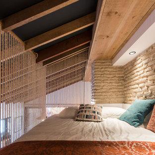 Cette image montre une petit chambre mansardée ou avec mezzanine méditerranéenne avec un mur beige et aucune cheminée.