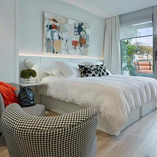Ejemplo de dormitorio principal, actual, de tamaño medio, con paredes blancas y suelo de madera clara