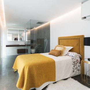 Imagen de dormitorio actual con paredes blancas, suelo de cemento y suelo gris