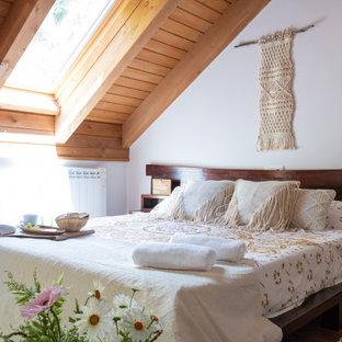 Modelo de dormitorio principal, rústico, de tamaño medio, con paredes blancas, suelo de madera oscura y suelo marrón