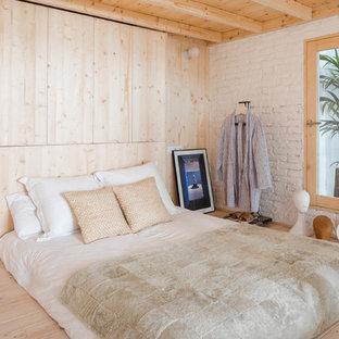 Imagen de dormitorio nórdico con paredes blancas, suelo de madera clara y suelo beige
