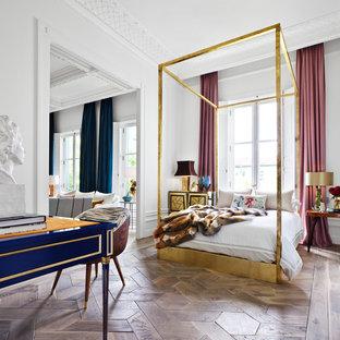 Modelo de dormitorio principal, bohemio, grande, sin chimenea, con paredes blancas y suelo de madera en tonos medios