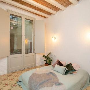 Imagen de dormitorio mediterráneo con paredes blancas y suelo multicolor