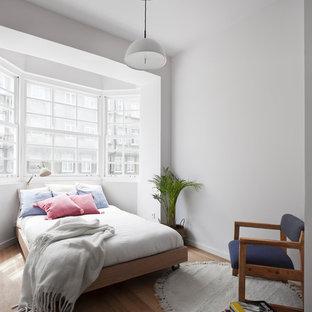 Modelo de dormitorio contemporáneo, sin chimenea, con suelo de madera en tonos medios y paredes blancas