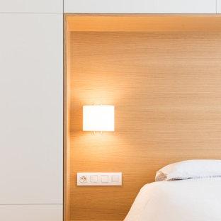 バルセロナのコンテンポラリースタイルのおしゃれな主寝室 (白い壁、無垢フローリング、暖炉なし、茶色い床) のインテリア