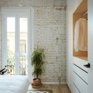 Imagen de dormitorio ladrillo, contemporáneo, ladrillo, con paredes blancas, suelo de madera clara, suelo beige y ladrillo