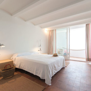 Mid-sized mediterranean master bedroom in Barcelona with white walls, terra-cotta floors and no fireplace.