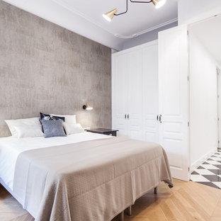 Modelo de dormitorio principal, contemporáneo, de tamaño medio, sin chimenea, con paredes grises, suelo de madera en tonos medios y suelo marrón