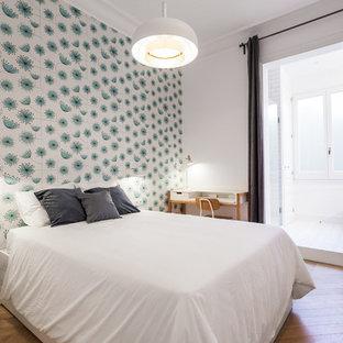 Imagen de dormitorio nórdico con paredes blancas, suelo de madera en tonos medios y suelo marrón