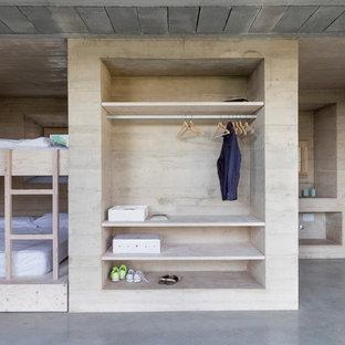 Imagen de habitación de invitados moderna con paredes beige, suelo de cemento y suelo gris