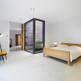 Modelo de dormitorio principal, actual, con paredes blancas, suelo de cemento y suelo gris