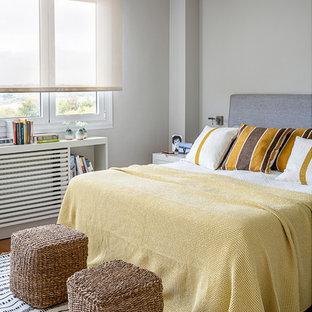 Foto de dormitorio actual con paredes grises, suelo de madera en tonos medios y suelo marrón