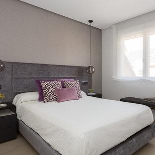 Ejemplo de dormitorio principal, actual, sin chimenea, con paredes grises, suelo de madera clara y suelo beige