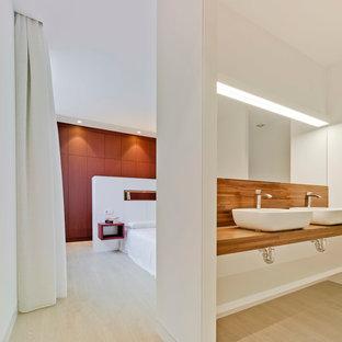 Modelo de dormitorio principal, contemporáneo, grande, sin chimenea, con paredes blancas y suelo de madera clara