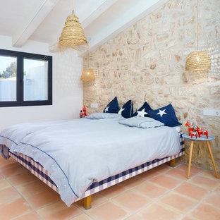 Ejemplo de dormitorio mediterráneo con paredes beige, suelo de baldosas de terracota y suelo naranja