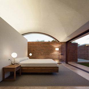 Пример оригинального дизайна: хозяйская спальня среднего размера в стиле модернизм с полом из травертина и бежевыми стенами без камина