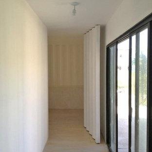 Пример оригинального дизайна: хозяйская спальня среднего размера в стиле лофт с белыми стенами, светлым паркетным полом и фасадом камина из штукатурки без камина