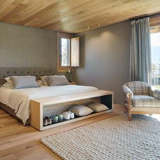 Modelo de dormitorio principal, de estilo de casa de campo, grande, con suelo de madera clara, paredes grises y suelo marrón
