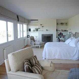 Ispirazione per una grande camera matrimoniale stile rurale con pareti gialle, pavimento in legno massello medio, camino lineare Ribbon e cornice del camino in intonaco