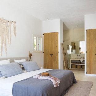 Imagen de dormitorio mediterráneo con paredes blancas y suelo beige