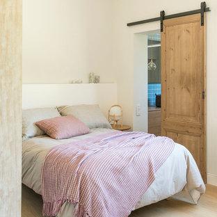Imagen de habitación de invitados mediterránea, de tamaño medio, sin chimenea, con paredes blancas, suelo de madera clara y suelo beige