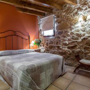 Imagen de dormitorio principal, rústico, de tamaño medio, sin chimenea, con parades naranjas y suelo de baldosas de cerámica