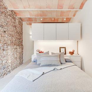 Diseño de dormitorio mediterráneo, de tamaño medio, sin chimenea, con paredes blancas, suelo de cemento y suelo gris