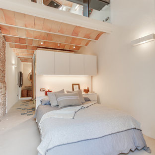Photo of a mid-sized mediterranean loft-style bedroom in Other with white walls, concrete floors and grey floor.
