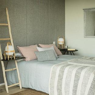 Modelo de dormitorio mediterráneo, de tamaño medio, con suelo de madera clara y paredes multicolor